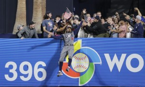 United States outfielder Adam Jones grabs a catch above the wall for the out on the Dominican Republic's Manny Machado during the seventh inning of a second-round World Baseball Classic baseball game Saturday, March 18, 2017, in San Diego. (AP Photo/Gregory Bull) ORG XMIT: CAGB137